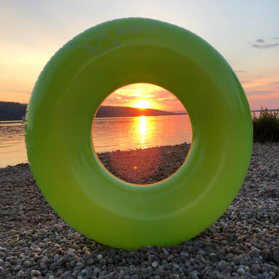 aspectra's green swim ring in the sunset at Greifensee | © Rita Tesenyi © aspectra AG